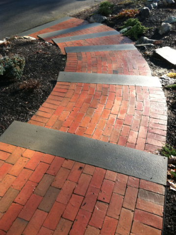 Brick pathway with stairs curving down a slope
