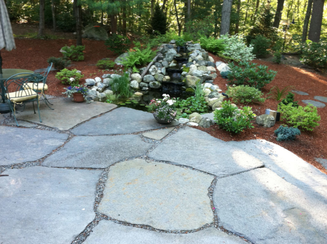 Landscaping beside patio with a water feature