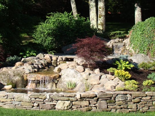 Water cascading through a garden into a pool of natural stone